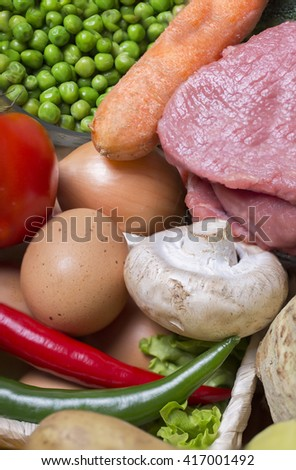 fresh meat with healthy vegetables and eggs placed on a wicker basket - close-up - stock photo