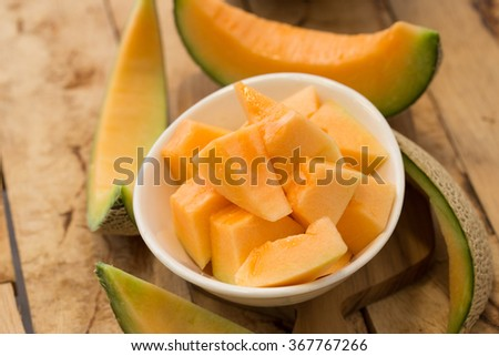 Fresh melons sliced in a bowl on old wooden table. - stock photo