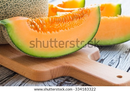 Fresh melons sliced on wooden table - stock photo