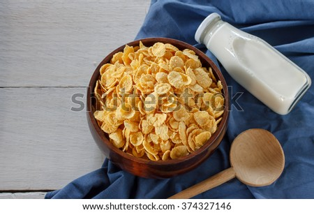 Fresh milk and cornflakes in a white bowl on a wooden table and blue cloth background. Organic healthy food rich in minerals and vitamins. Eco food for breakfast. - stock photo