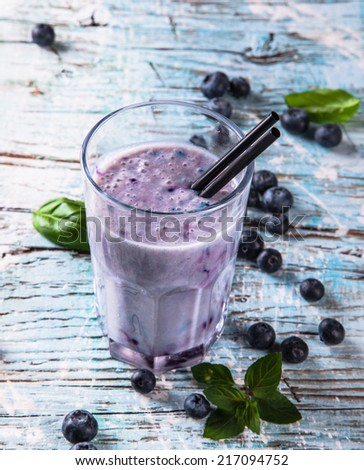 Fresh milk, blueberry drink on wodeen table, assorted protein cocktail with fruits. - stock photo