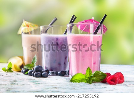 Fresh milk, raspberry, blueberry and banana drinks on wooden table, assorted protein cocktails with fresh fruits.   - stock photo