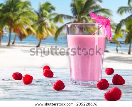 Fresh milk, raspberry, on wooden table, assorted protein cocktails with fresh fruits. Tropical beach background. - stock photo