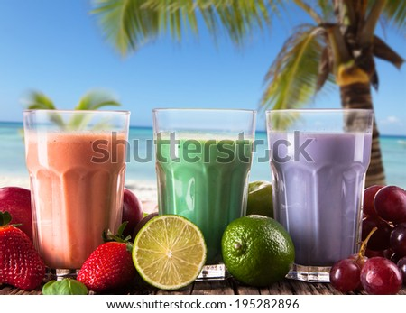 Fresh milk shake, strawberry, lime and grape on wooden background with tropical beach, assorted protein cocktails with fruits.  - stock photo