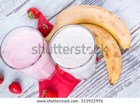 Fresh milk,strawberry and banana drinsk on wooden table, assorted protein cocktails with fresh fruits.  - stock photo