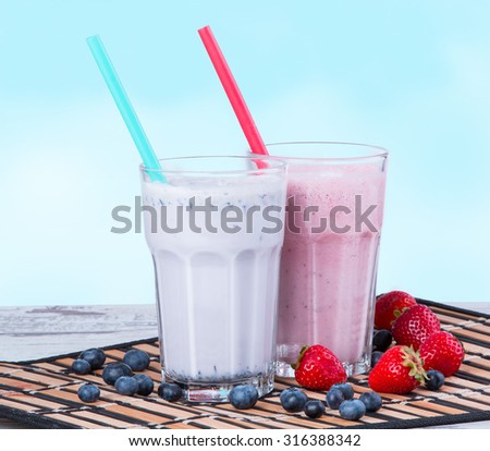 Fresh milk, strawberry and blueberry drinks on wooden table, assorted protein cocktails with fresh fruits. - stock photo