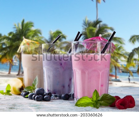Fresh milk, strawberry, blueberry and banana on wooden table, assorted protein cocktails with fresh fruits. Natural background. Tropical beach - stock photo