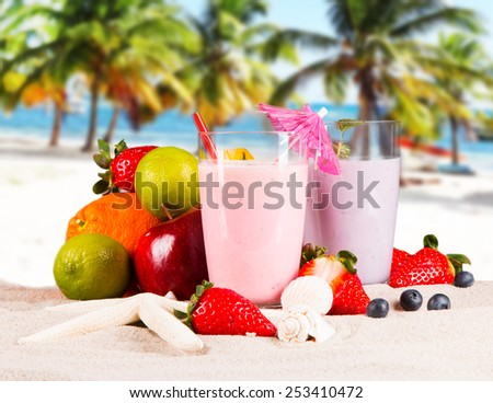 Fresh milk, strawberry, blueberry drinks on wooden table, assorted protein cocktails with fresh fruits and tropical beach background. - stock photo