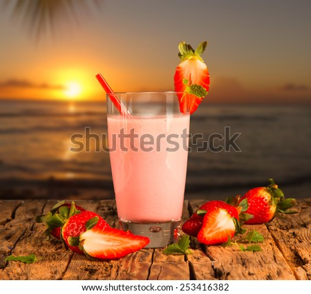 Fresh milk, strawberry drink on wodeen table, assorted protein cocktail with fresh fruits and tropical beach background  - stock photo