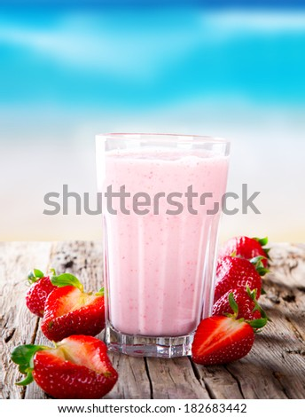 Fresh milk, strawberry drink on wodeen table, assorted protein cocktail with fresh fruits. Summer drink on the beach and blue sky.  - stock photo