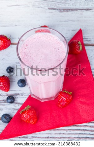 Fresh milk, strawberry drink on wooden table, assorted protein cocktail with fresh fruits. - stock photo