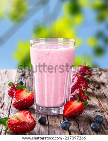 Fresh milk, strawberry on wooden background, assorted protein cocktail with fruits. - stock photo