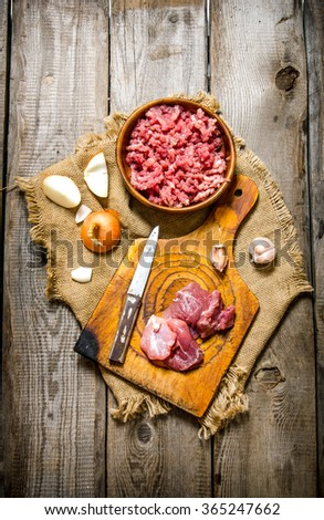 Fresh minced meat with spices and oil. On a wooden table. Top view - stock photo