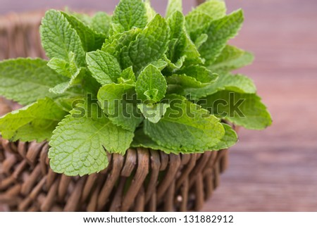 fresh mint leaves on a wooden background - stock photo