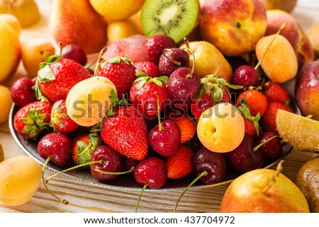 Fresh mixed fruits, berries on plate. Summer fruit, berry. - stock photo
