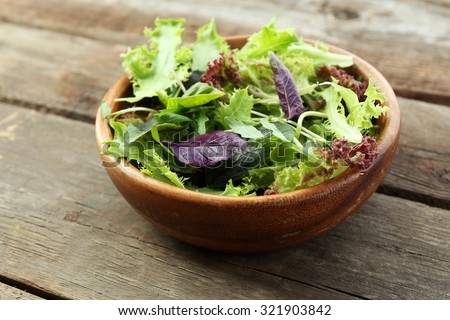 Fresh mixed green salad in bowl on wooden table close up - stock photo