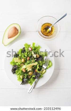 Fresh mixed green salad with avocado on white plate overhead shoot - stock photo