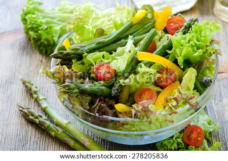 Fresh mixed spring salad with green asparagus, tomatoes and paprika - stock photo