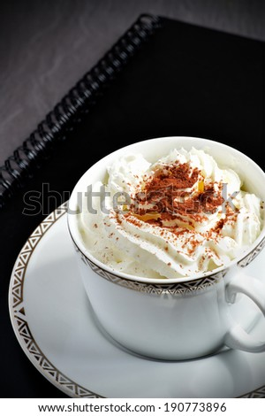 Fresh mocha coffee in elegant coffee cup and saucer on a black business file. Concept image for a relaxed business meeting. Copy space.  - stock photo