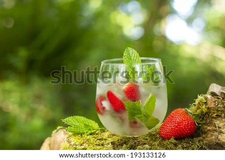 Fresh mohito with ice and strawberries outdoor - stock photo