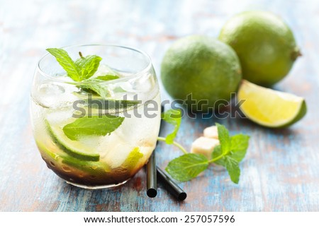 Fresh mojito cocktail on bamboo place-mat. Over blue rustic background. Focus on  frontal part of glass, lime and mint leaves in it. - stock photo