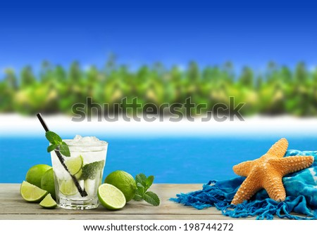 fresh mojito cocktail, starfish and sarong in a tropical landscape - stock photo