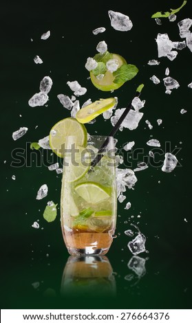 Fresh mojito drink with ice cubes and splashes on black background - stock photo