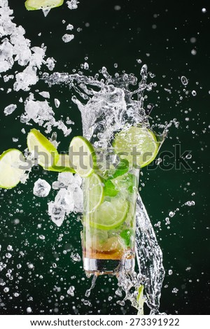 fresh mojito drink with liquid splash and drift, freeze motion. - stock photo