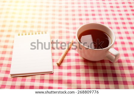 Fresh morning with black coffee with note paper and pencil on wood table. Vintage light filter. - stock photo