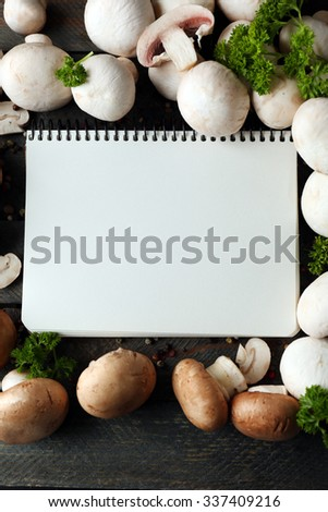 Fresh mushrooms and empty notebook on wooden background - stock photo