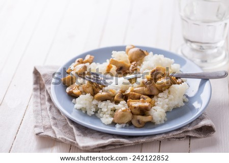 Fresh mushrooms and rice on plate on white table. Selective focus. Rustic style.  - stock photo