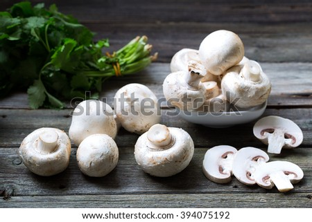 Fresh mushrooms champignons on wooden background - stock photo