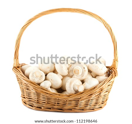 Fresh mushrooms in a wicker basket isolated on white background - stock photo