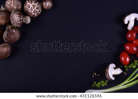 Fresh mushrooms with spices and herbs on a black board. - stock photo