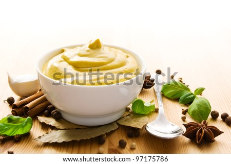 Fresh mustard in a bowl with spices and a spoon