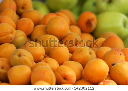 Fresh natural apricot and apples to background on the street market - stock photo