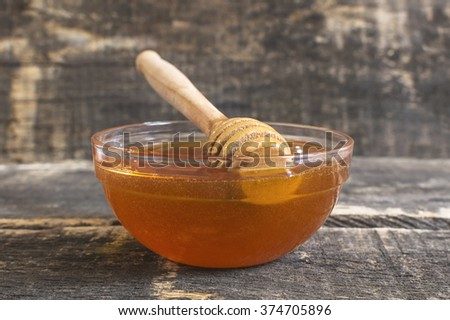 Fresh natural bee honey in a glass jar with spoon deeper on a wooden rustic vintage table. Selective focus. - stock photo