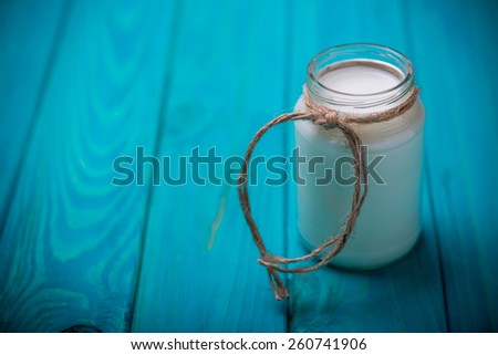 fresh natural healthy bottle with milk product and twine decoration on blue wooden background - stock photo