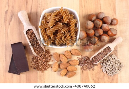 Fresh, natural ingredients and products containing magnesium and dietary fiber, healthy food and nutrition, wholemeal pasta, buckwheat, linseed, almonds, hazelnut, chocolate - stock photo