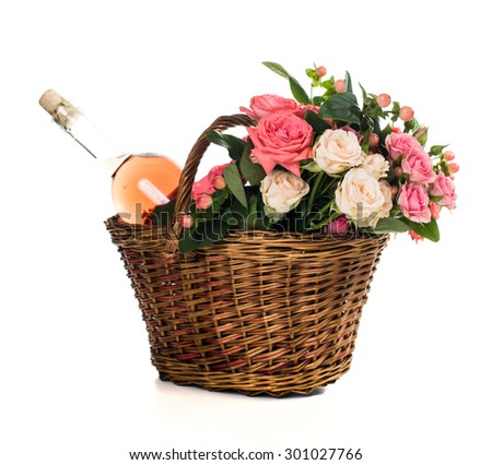 Fresh natural pink roses in a wicker basket  and a bottle of rose wine on white background isolated. Fruits, wine and flowers. - stock photo