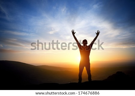 Fresh New Morning - A person reaching up on a bright morning sunrise. - stock photo