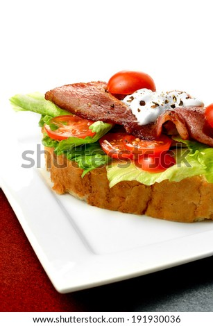 Fresh oak smoked cured bacon with mayo, iceberg lettuce, tomatoes and black cracked pepper sandwich against a white background. Copy space.