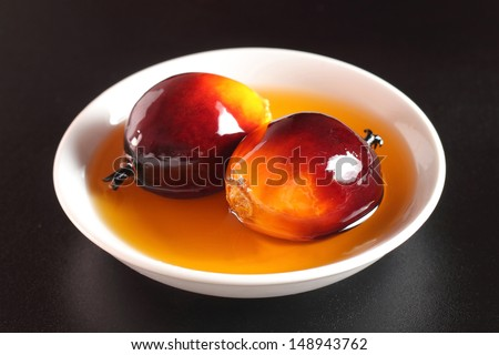 Fresh oil palm fruits and cooking oil on white plate - stock photo