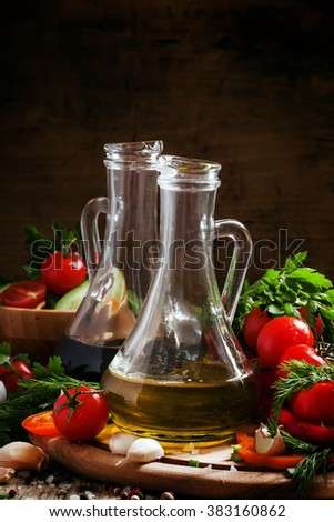 Fresh olive oil in glass carafe with tomatoes, peppers, cucumbers, garlic, herbs and spices on a dark wooden background, selective focus - stock photo