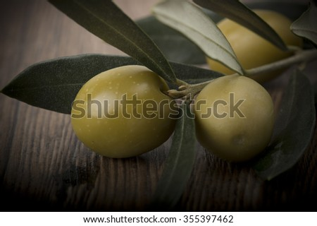 Fresh olives and leaves on the wooden table