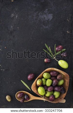 Fresh olives on black rustic background - stock photo