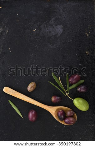 Fresh olives on black rustic background - stock photo