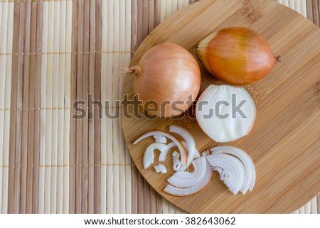 Fresh onions sliced on a cutting board, top view - stock photo