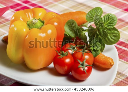Fresh, orange bell pepper, basil, cherry tomatoes and carrot served on a white plate on the table - vegetable, herb, curative, vegan food. - stock photo