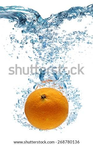 Fresh orange dropped into water with splash isolated on white - stock photo